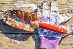 Садовничая лопата перчатки и сада на деревенской деревянной таблице Стоковое Фото