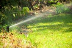 Садоводство Вода спринклера лужайки распыляя над травой Стоковые Фотографии RF