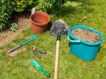 Садовые инструменты лежа на траве с ящиком полным почвы Стоковое Изображение RF