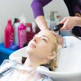 Салон парикмахера Женщина во время мытья волос Стоковые Фото
