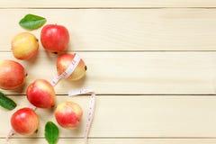 Салфетка яблока взгляд сверху красная, нож, корзина, измеряя лента на деревянном Стоковые Изображения RF