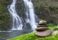 Сбалансированный стог Дзэн утеса перед водопадом стоковая фотография rf