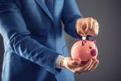 сбережениа дег банка piggy кладя Бизнесмен держа розовую piggy и кладя монетку в копилку Стоковое Фото