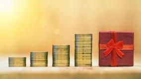 Сбережения денег - золотые монетки и красная подарочная коробка Стоковые Фотографии RF