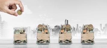 Сбережения денег, рука кладя монетку в стеклянный опарник с монетками внутрь, с предпосылкой города Стоковое Изображение