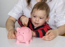 Сбережения на будущее Маленькая девочка кладет монетки в piggy банк денег Стоковые Изображения RF