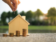 Сбережения для того чтобы купить дом которое вручает установку денег стога монеток денег растя, сохраняя или концепции роста дене Стоковое Изображение