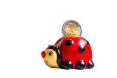 Сбережения Ladybug кладут в коробку или банк монетки с евро 2 в ем изолировал на белой предпосылке стоковое изображение rf