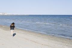 Сбрасывание молодой женщины идя пляжем стоковое фото