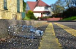 Сброшенная пластичная бутылка лежа на крае городской улицы Стоковые Изображения