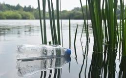 Сброшенная пластичная бутылка плавая в озеро Стоковые Изображения