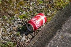 Сброшенная пустая консервная банка кока-колы/кокса в улице стоковая фотография