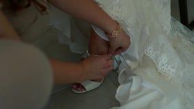 Свадьба, подруга помогает зафиксировать ботинки белизны ` s невесты акции видеоматериалы