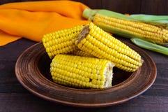 Сваренные и сырцовые стержни кукурузного початка на темной деревянной предпосылке Стоковое фото RF