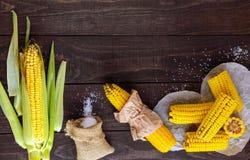 Сваренные и сырцовые стержни кукурузного початка на темной деревянной предпосылке Стоковая Фотография RF