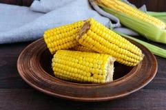 Сваренные и сырцовые стержни кукурузного початка на темной деревянной предпосылке Стоковое Изображение RF