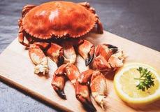 Сваренные крабы закипели на деревянной доске с лимоном на черной плите служили морепродукты - красный коготь каменного краба стоковое фото