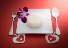 Сваренный рис с ложкой и вилка на белых блюде и орхидее Стоковые Изображения