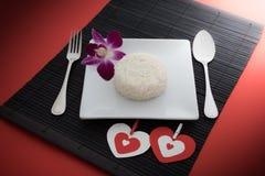 Сваренный рис с ложкой и вилка на белых блюде и орхидее Стоковые Фото