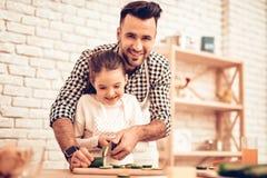 Сварите еду дома семья счастливая отец s дня Еда повара девушки и человека Человек и ребенок на таблице Потратьте время совместно стоковая фотография rf