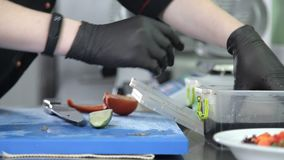 Сварите с перчатками на подготовке салата в кухне ресторана сток-видео