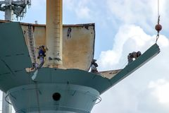 Сварщики принимают врозь разделы старой водонапорной башни с их факелами Стоковое Фото
