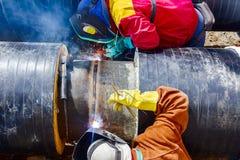 Сварщики работая на трубопроводе. Стоковые Изображения
