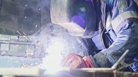 Сварщик взгляда со стороны в сваривая маске сваривает 2 части металла Рабочий класс в coveralls работает внутри помещения сток-видео
