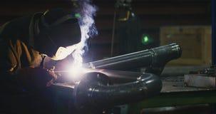 Сварщик в сваривая маске, в одеждах деятельности на фабрике, сваривает трубу в комнате фабрики сток-видео