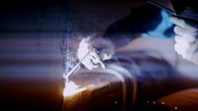 Сварщик газа работает на объекте Работа газосварочной машины на темной предпосылке сток-видео