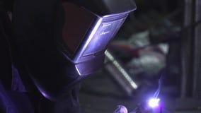 Сварщик конца-вверх в защитной одежде работая с металлом, металлом заварки r Сваривая процесс видеоматериал