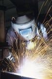 Сварщик нося защитную заварку лицевого щитка гермошлема на работе Стоковое Изображение RF