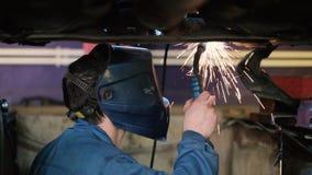 Сварщик работая под автомобилем видеоматериал