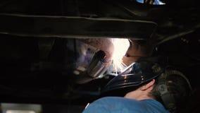 Сварщик работая под автомобилем сток-видео