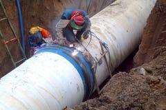 Сварщик сваривает большую стальную трубу водопровода стоковое изображение rf