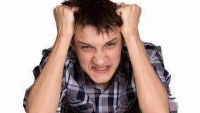 Сварливый молодой человек на серой предпосылке Стоковая Фотография RF