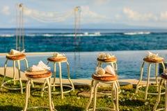 Свадебная церемония настроила около океана на заходе солнца - стульев для гостей с лепестками цветка и бамбуковыми вентиляторами  стоковые изображения