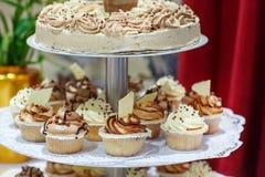 Свадебный пирог и пирожные в коричневом цвете и сливк. стоковые фото