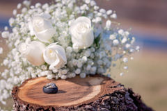 Свадьба и обручальные кольца на деревянном пне с белыми розами Стоковые Фотографии RF