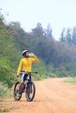 Свежая вода молодого человека велосипеда (велосипедиста) выпивая от пластмассы bo Стоковые Фото