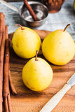 Свежая желтая груша на деревянной доске, ручки циннамона, конец вверх Стоковое Изображение RF