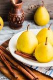 Свежая желтая груша на деревянной доске, ручки циннамона, селективные Стоковое Изображение