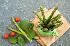 Свежая зеленая спаржа в томатах кружки, шпината и вишни Стоковые Фотографии RF