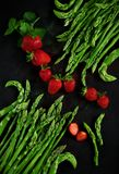 Свежая зеленая спаржа наклоняет при красные украшенные клубники красиво аранжированными на темной деревянной плите Стоковое фото RF
