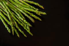 Свежая зеленая спаржа на черноте еда вареников предпосылки много мясо очень стоковые фотографии rf