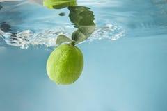 Свежая известка в воде изолированной на голубой предпосылке Стоковые Изображения