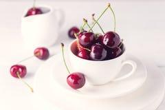 Свежая и красивая вишня в предпосылке белизны вишни белой чашки зрелой сочной Стоковые Изображения