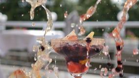 Свежая концепция коктейля лета Ягоды и кубы льда брызгают падать вниз в gluss с красиво украшенным плодом видеоматериал