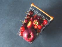 Свежая красная тележка супермаркета ягод плодоовощ на черноте Стоковое Фото