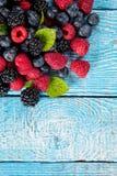 Свежая куча плодоовощ ягоды помещенная на старых деревянных планках стоковое фото rf